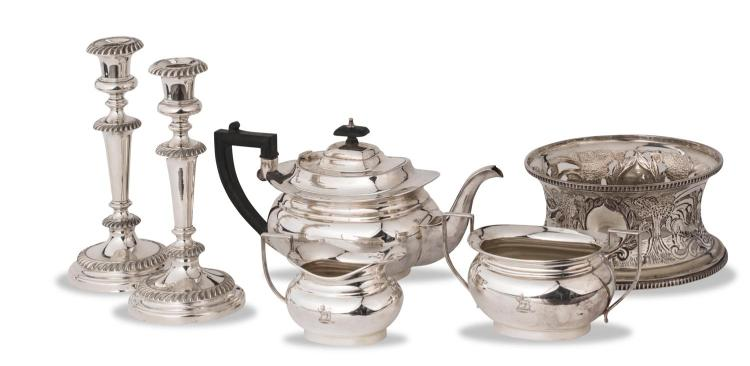 A collection of silver plates including a three piece tea set, a potato ring, a pair of candlesticks, English