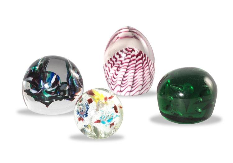 A collection of four glass paperweights