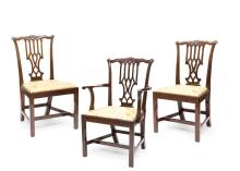 A set of fourteen George III mahogany dining chairs,comprising twelve dining chairs and two carvers, each with pierced Gothic splat above a drop in seat