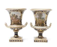 A pair of campana form Crown Derby urns, early 19th centuryeach painted with a bucolic scene within a gilt cartouche on a blue groundone inscribed: Near Loughborough, Leistershirethe other inscibed: In South Wales33 cm high (each)