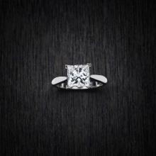 A 3.20 carat solitaire diamond ring, the four-claw set princess cut diamond of known weight. Platinum. Weight 6.76 grams. Size O.