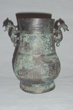 A Rare Zhou Dynasty Bronze Wine Vessel with Archaic Motifs and Dragon-Handles