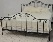 King size iron bed, complete with frame, mattress, box springs, bedspread, three shams, and skirt. ht. 54 in.