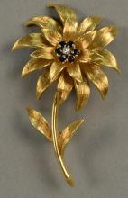 18K Tiffany brooch in form of flower set with six blue sapphires and a center diamond. ht. 2 1/4in. 15.7 grams
