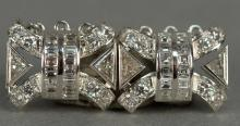 Two platinum and diamond clasps of rectangular form set with a combined total of sixteen full cut diamonds, four trillion cut diamon...