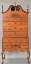 Chippendale cherry high chest in two parts, upper section with full bonnet top on lower section with carved skirt set on cabriole le...