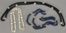 Three necklaces including a necklace with small pearls, one lapis, and one black onyx.