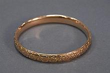 14K gold bangle bracelet with floral motif, marked inside 1906. 15.1 grams 2 5/8