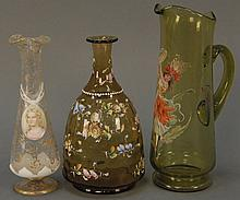 Three enameled pieces to include enamel flower vase, pitcher with enameled girl, and a clear glass vase with enameled plaque possibl...