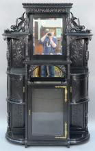 Kimbel & Cabus aesthetic ebonized etagere having centered mirror flanked by carved winged dragons over shelves and two bowed doors a...