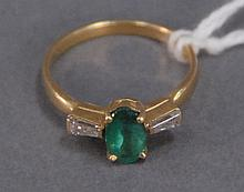 18K gold ring set with oval emerald flanked by small diamonds.