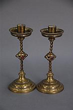 In the manor of Edward Pugin, pair of brass candlesticks, each having drip tray over twisted stem and knob set with four ruby glass...