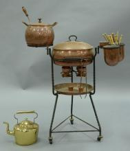 LA Monda copper fondue set on turned iron stand having center oval pot with iron hinges over burners, hand hammered. ht. 39in., wd....