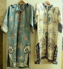 Two silk embroidered robes including one white with embroidered blue flower and fine border, flaming clouds, and six round panels wi...