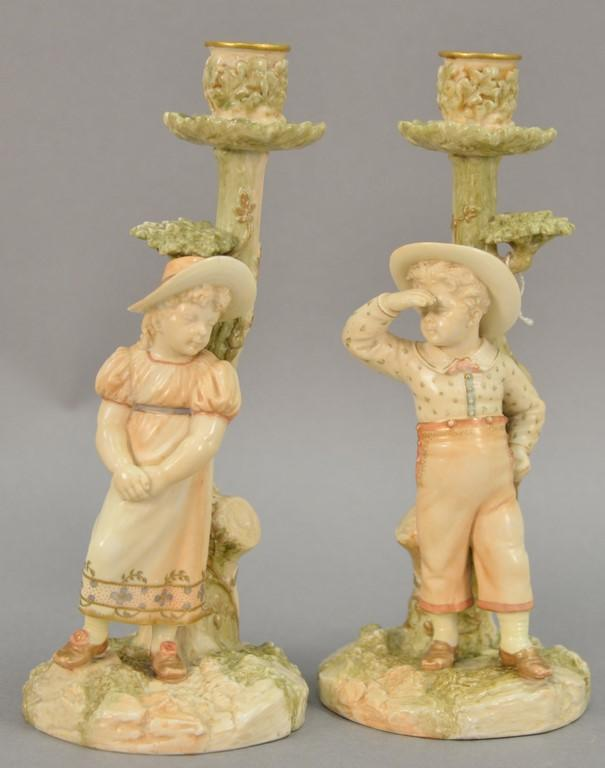 Pair of Royal Worcester figural candlesticks, boy and girl with hats, signed on base: Hadley, marked with pruple mark. ht. 10 1/4in.