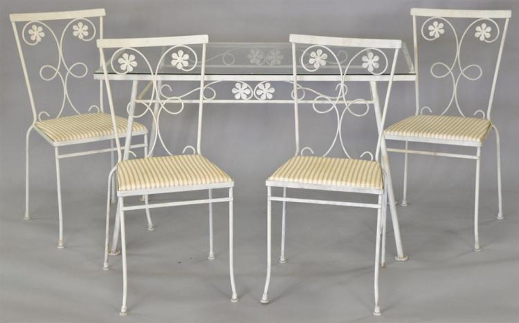 Wrought iron glass top table and four chairs.