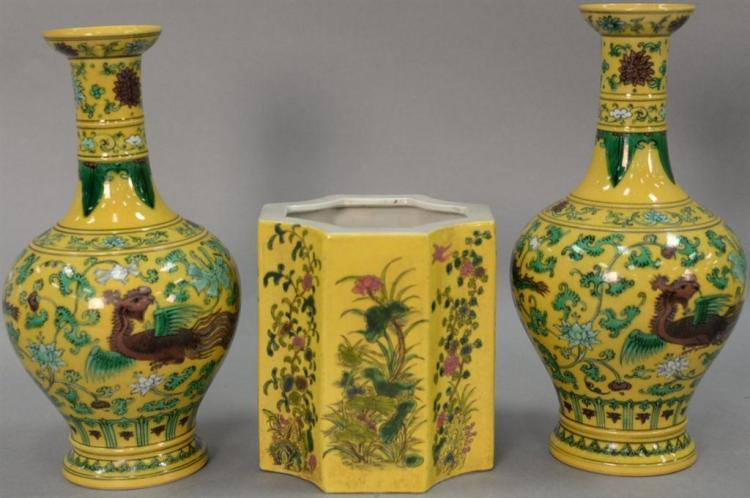 Three Famille Rose yellow ground Chinese porcelain pieces to include a pair of dragon vases and an octogon pot. vases: ht. 11 1/2