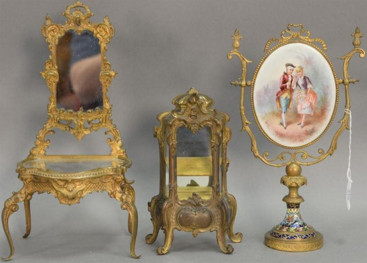 Three piece lot to include a brass enameled vanity mirror with porcelain painted plaque (12in.), small brass French style cabinet (8...