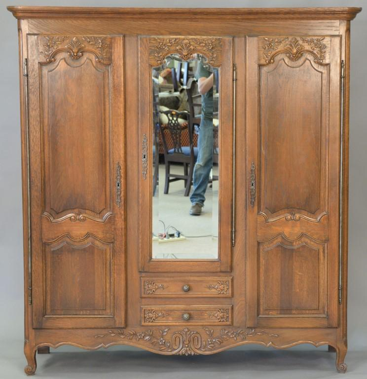 Oak three door cabinet. ht. 70 1/2in., wd. 66 1/2in., dp. 16in.
