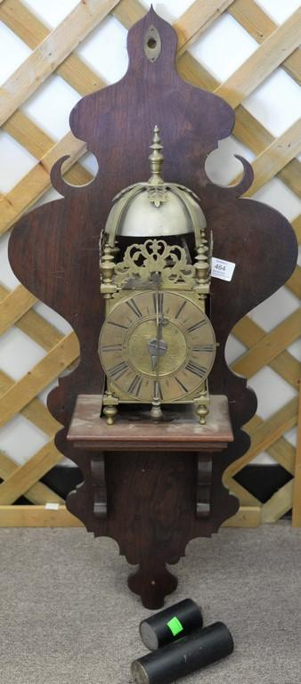 Brass skelton clock with chime dome top, brass works, and mahogany wall shelf.