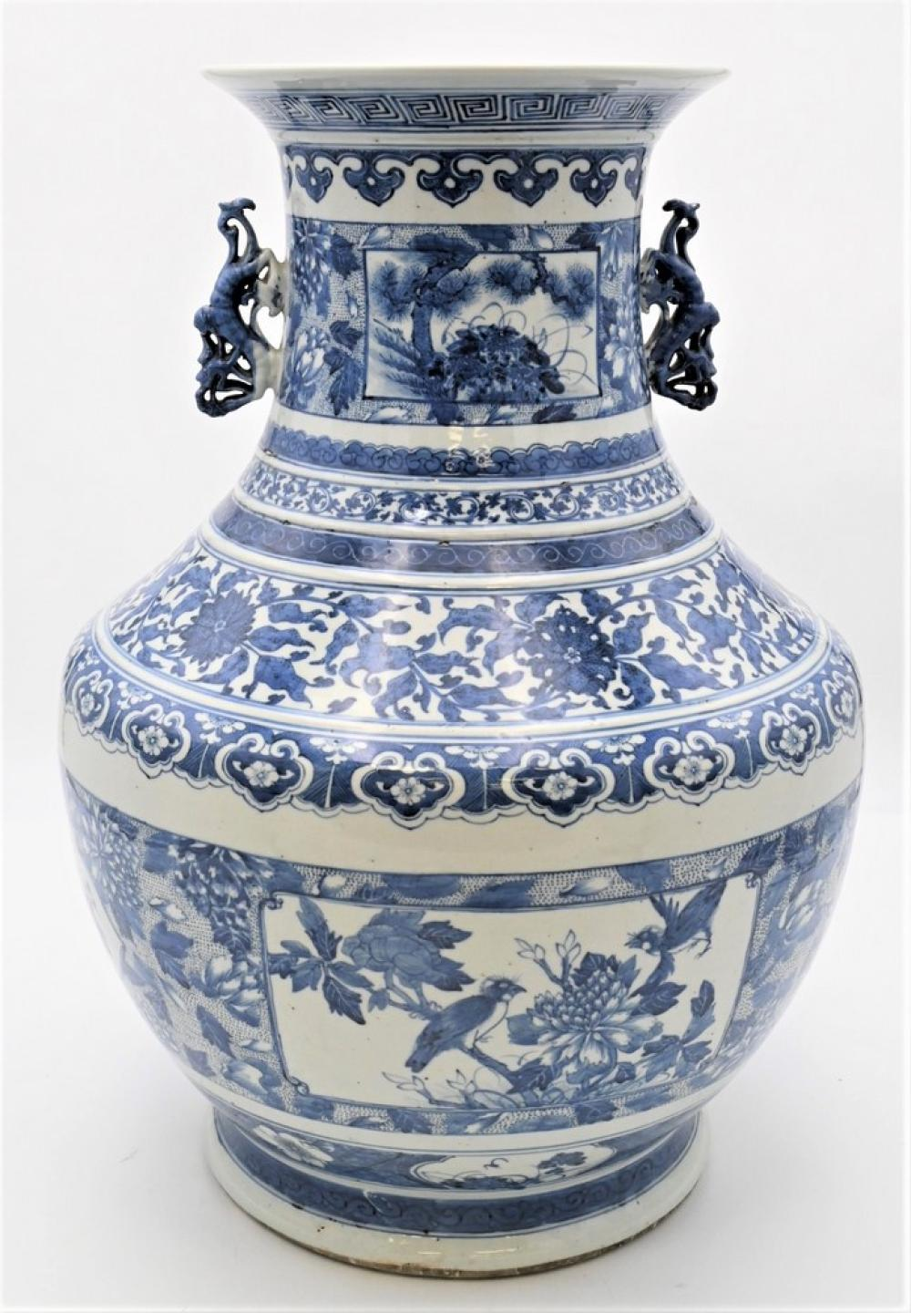 Large Chinese Blue and White Urnhaving flared rim over dragon handles with bulbous body, painted flowers and panel scenes with bir...