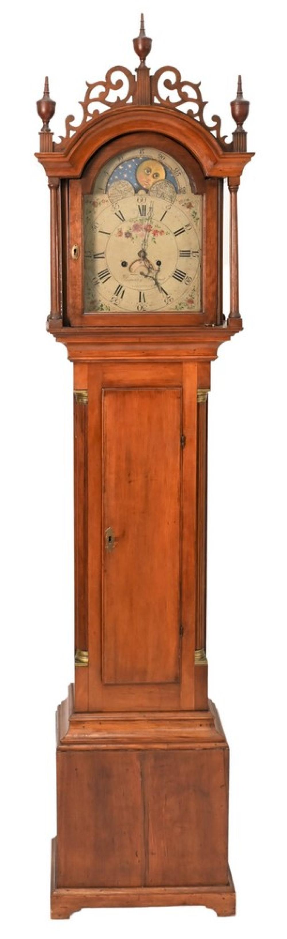 Timothy Barnes Cherry Tall Clockhaving fret work top with three wood finials supported by fluted columns over long door flanked by ...