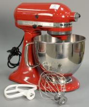 Red KitchenAid artisan mixer with attachments.