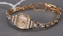 14K gold ladies wristwatch including band, set with diamonds, 18.3 grams total weight.