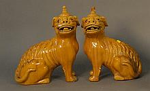Pair of glazed porcelain foo dogs (one lip chipped, two finials repaired), ht 17in.