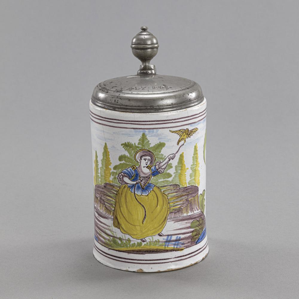 A GERMAN PEWTER MOUNTED FAYENCE TANKARD WITH A LADY