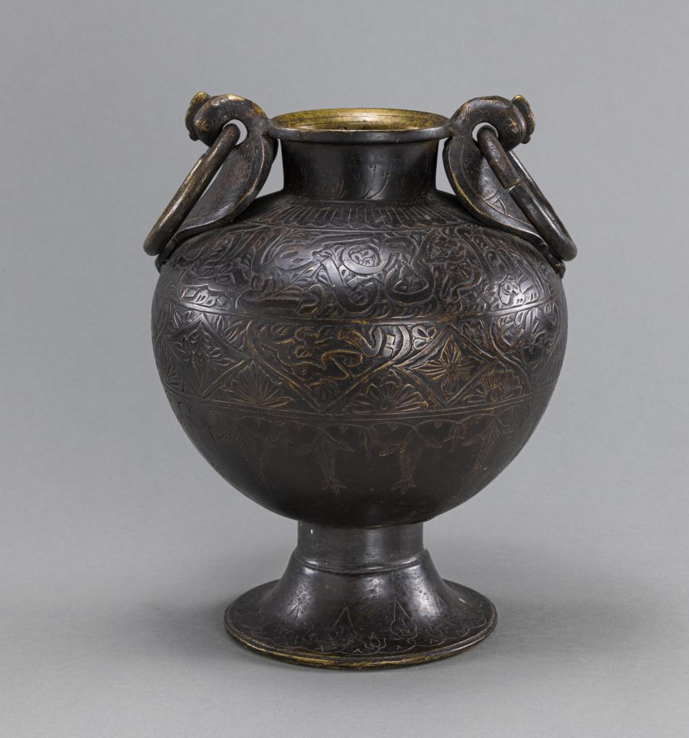 A FINELY ENGRAVED FOOTED BRASS VASE IN SHAPE OF AN AMPHORA WITH BIRD-SHAPED HANDLES