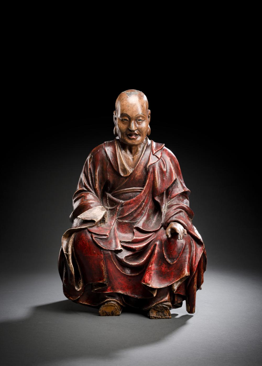 A POLYCHORME-LACQUERED WOOD FIGUR OF A SEATED MONK
