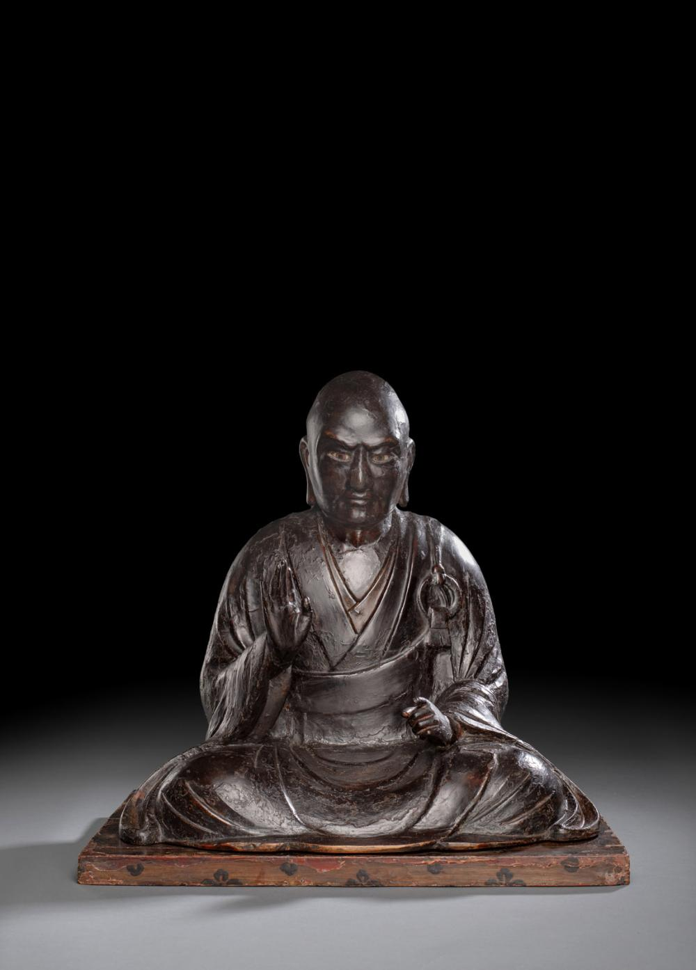 A CARVED AND LACQUERED WOOD FIGURE OF A SEATED PRIEST