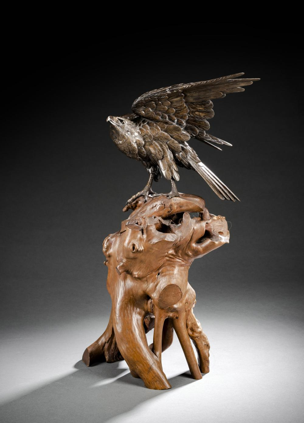 A BRONZE MODEL OF AN EAGLE ON A ROOTWOOD STAND