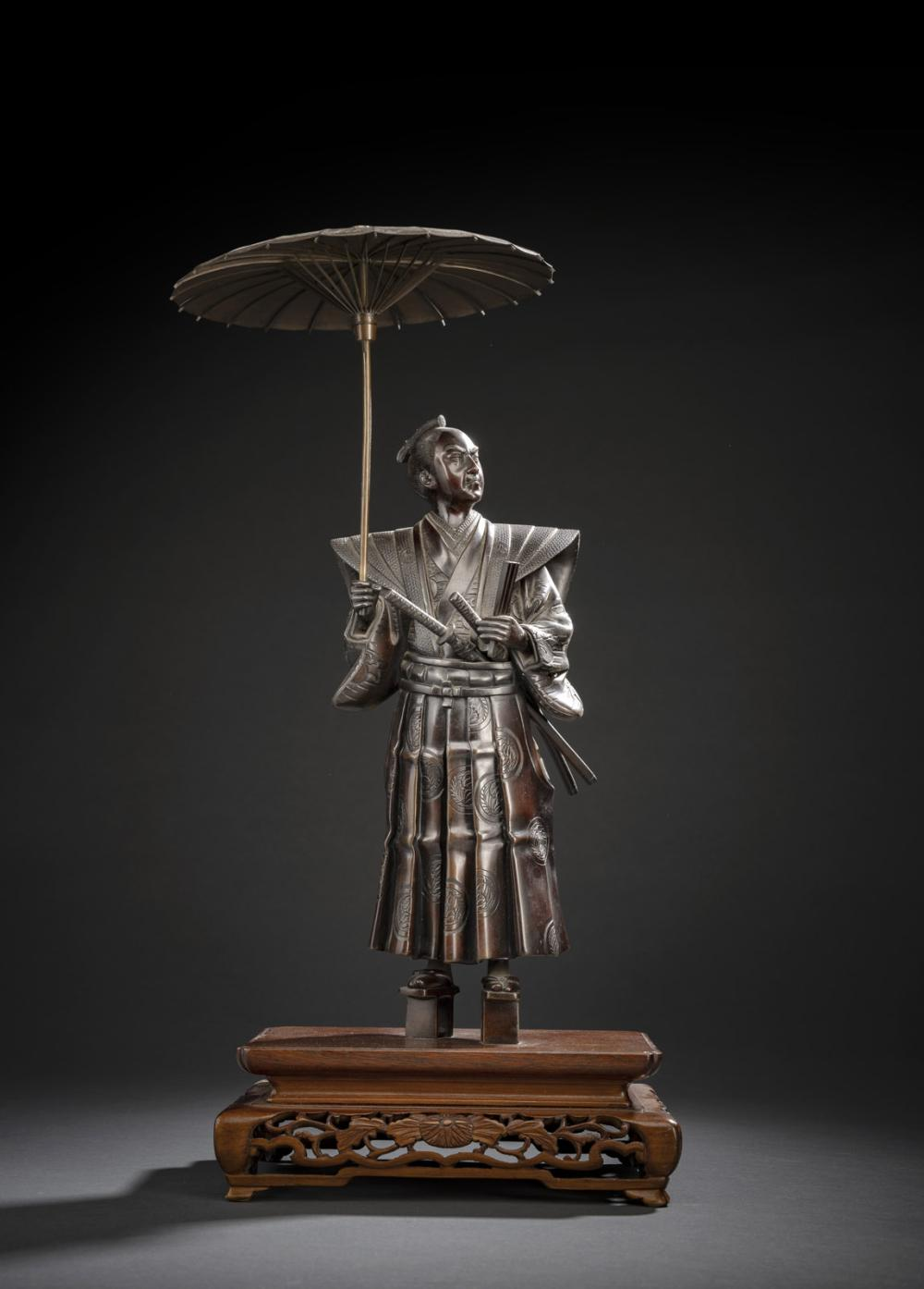 A BRONZE FIGUR OF A STANDING COURTIER HOLDING AN OPEN PARASOL AND A FAN