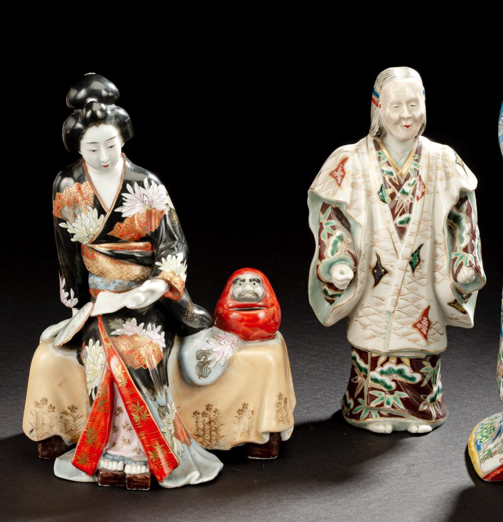 TWO POLYCHROME PAINTED KUTANI PORCELAIN GROUPS OF AN ACTOR WEARING A NÔ MASK AND A READING BIJIN WITH A DARUMA DOLL