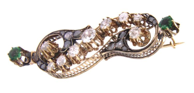 An antique 9k gold brooch with old cut diamonds and two green stones