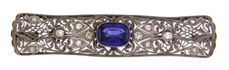 An 9k white gold art deco filigree brooch with a sapphire and diamonds.