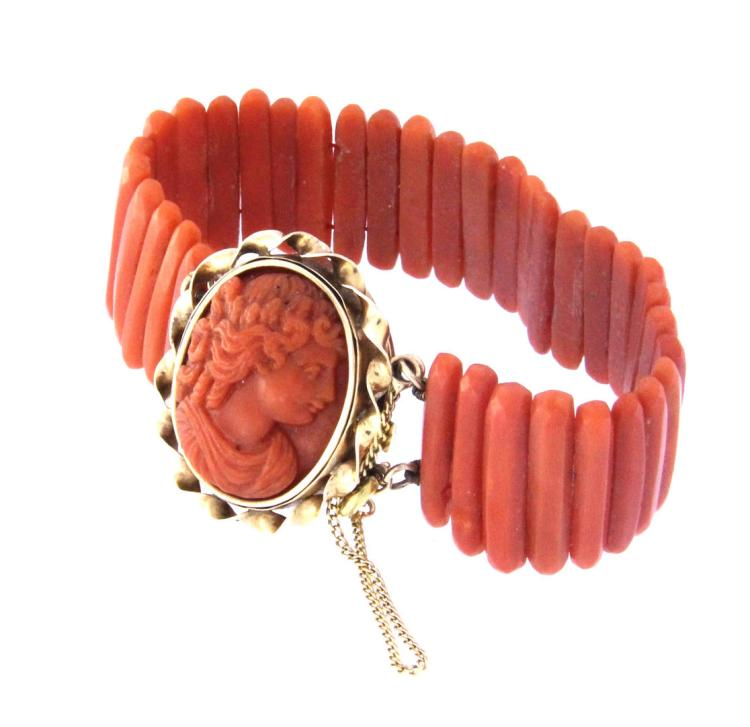 An antique red coral bracelet with 18k yellow gold clasp and a red coral carved cameo.