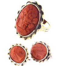 An antique 18k yellow gold pair of ear-clips and ring set with three carved red coral cameo.