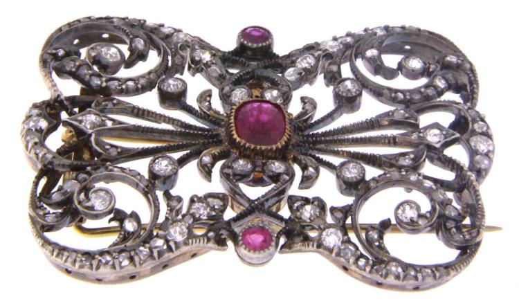 An antique 18k white gold art deco filigree brooch with ruby and diamonds.