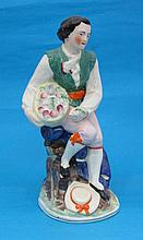 A Staffordshire figure of a seated youth, holding