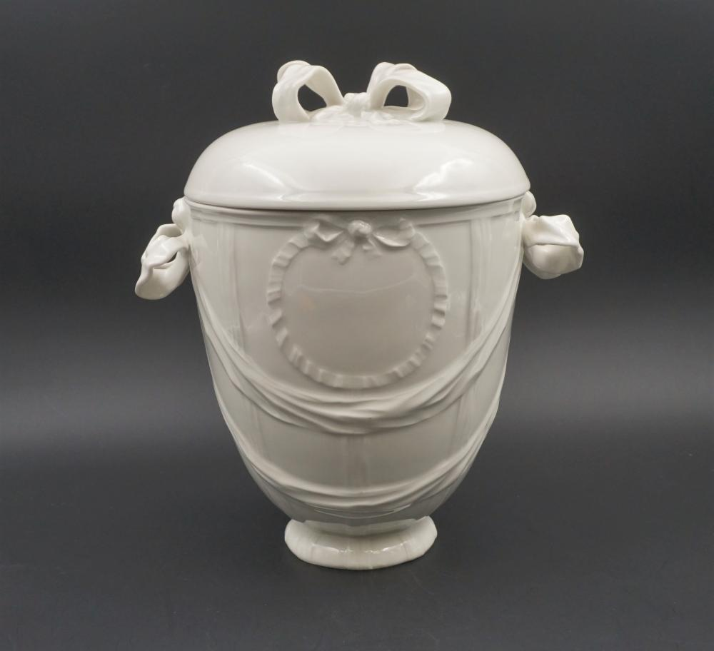 Cream-colored ceramic urn with ribbons