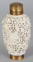 A CHINESE WHITE GLAZED PORCELAIN SNUFF BOTTLE, mounted as a scent bottle with brass fittings, the sides moulded in deep relief with a dragon and a phoenix amidst cloud scrolls, 3.25in high.