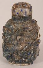 A CHINESE LAPIS SNUFF BOTTLE & STOPPER, the sides carved in deep relief with two phoenix above flowers and leafage, 3.1in high.