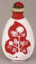 AN UNUSUAL CHINESE WHITE OVERLAY GLASS SNUFF BOTTLE & STOPPER, the pear form body decorated with two shaped panels of flowers and rockwork reserved on a red ground, 3.6in high.