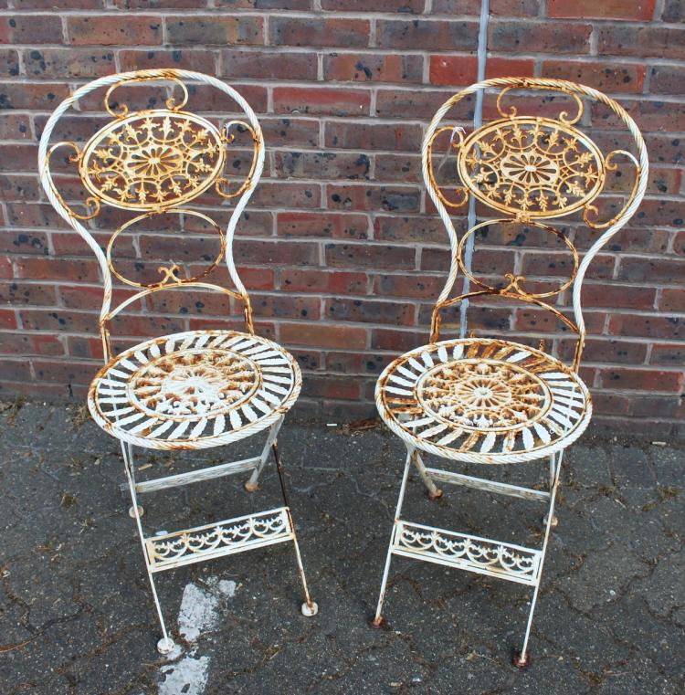 a pair of white painted wrought iron chairs