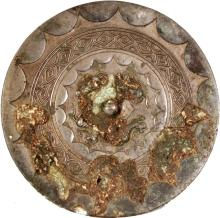 A CHINESE SILVERED BRONZE CIRCULAR MIRROR, possibly Song Dynasty, the top surface with formal designs and pronounced patinated encrustations, 5.4in diameter.