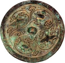 A SMALL CHINESE BRONZE MIRROR, possibly early, decorated in relief with birds and phoenix encircling a raised central boss, the whole with red and green patination, the central boss with small traces of gilding, 4.25in diameter.