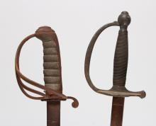 AN INFANTRY SWORD, straight back-edged blade with single fuller, brass hilt with double shell guard, reeded grip, ovoid pommel and knuckle bow, 39-inches, 19th century, rusted; and a rifle regiment type sword, slightly curved blade with single fuller, three bar hilt with shagreen grip, 38.25-inches, 19th century, rusted overall (2).